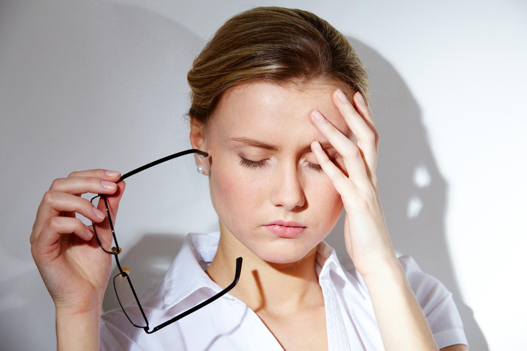 Portrait of young businesswoman having headache pains